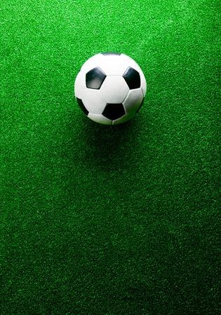 pelota de futbol: balón de fútbol con césped artificial, tiro del estudio sobre fondo verde. Espacio de la copia.