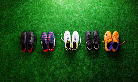 cleats: Various colorful cleats against artificial turf, studio shot on green background. Flat lay, copy space. Stock Photo