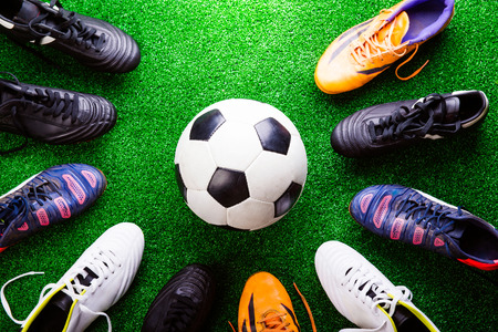 cleats: Soccer ball and cleats against artificial turf, studio shot on green background. Stock Photo