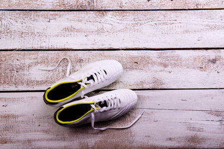 cleats: Soccer cleats against wooden floor, studio shot on white background. Copy space.