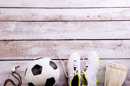protectors: Soccer ball, cleats, protectors and whistle against wooden floor, studio shot on white background. Flat lay, copy space Stock Photo