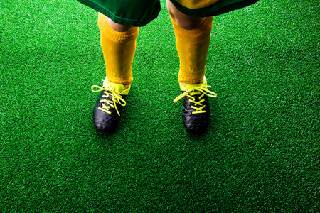cleats: Legs of unrecognizable little football player in cleats against artificial grass. Studio shot on green grass. Copy space.