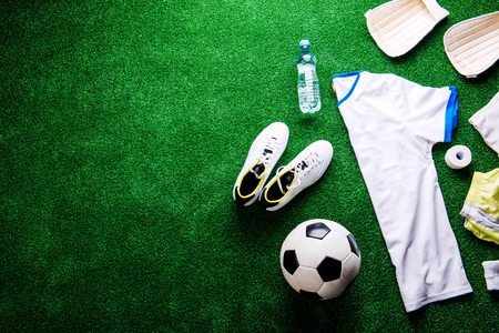 cleats: Soccer ball,cleats and various football stuff against artificial turf. Studio shot on green background. Copy space.