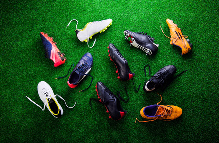 cleats: Various colorful cleats against artificial turf, studio shot on green background. Flat lay.