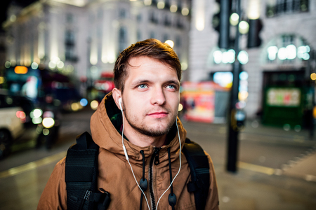 street night: Young hipster man with earphones, listening music, walking in the streets of London at night