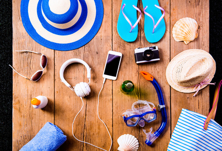 flip phone: Summer vacation composition with smart phone, camera, pair of flip flop sandals, hat, sunglasses, sun cream and other stuff on a wooden background, studio shot, flat lay.