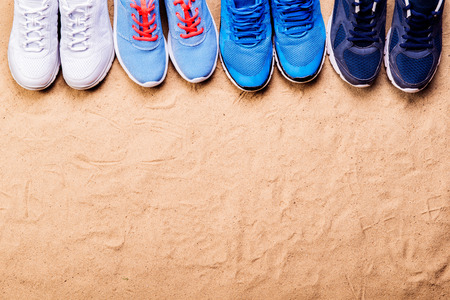 Various sports shoes in a row against sand background, studio shot, flat lay. Copy space.
