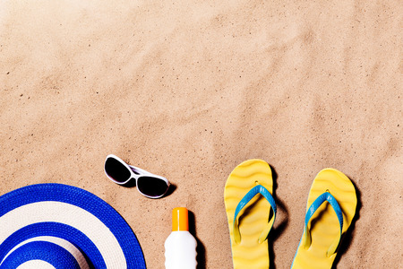 Summer vacation composition with a pair of yellow flip flop sandals, hat, sunglasses and suntan cream on a beach. Sand background, studio shot, flat lay. Copy space.
