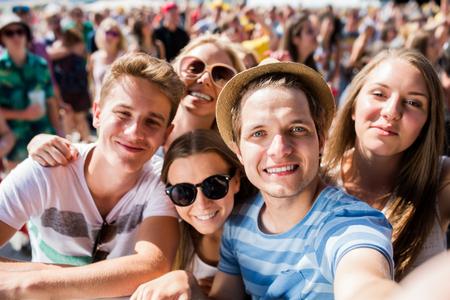 楽しんで撮影 selfie、群衆の中に夏の音楽祭でティーンエイ ジャー