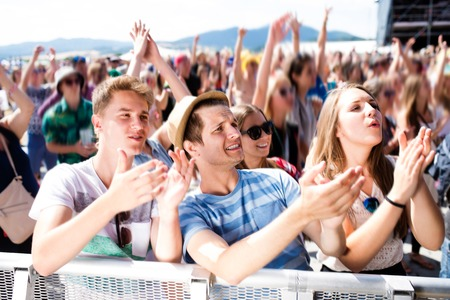 Teenagers at summer music festival under the stage in a crowd enjoying themselves, clapping, singing