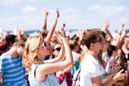 Tieners bij zomers muziekfestival onder het podium in een menigte genieten van zichzelf, arm verhoogd Stockfoto