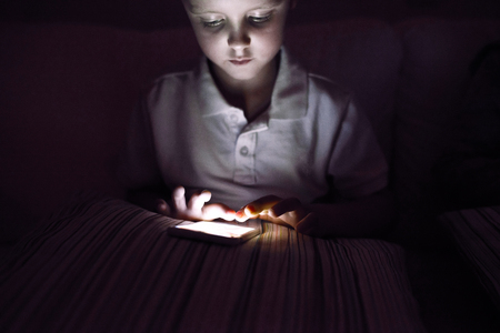 child boy: Little boy playing with smart phone, sitting on sofa in dark room at night.