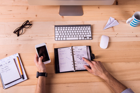 personal organizer: Businessman at the desk, wearing smart watch, working on smart phone. Personal organizer, computer and various office supplies around the workplace. Stock Photo