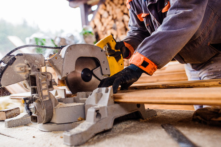 construction workers: Hands of unrecognizable carpenter working. Man using circular saw to cut planks of wood for home construction