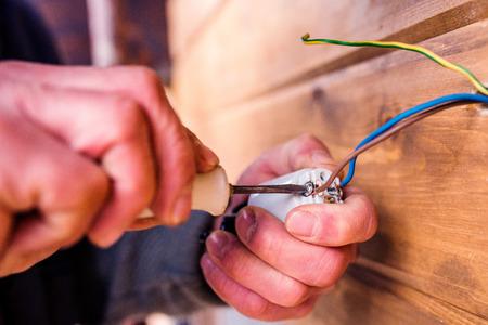 Handen van onherkenbare elektricien die werken met een schroevendraaier, houten muur