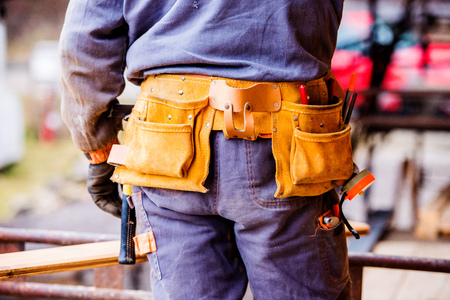 tool bag: Close up of unrecognizable construction worker with tool bag on site, rear view