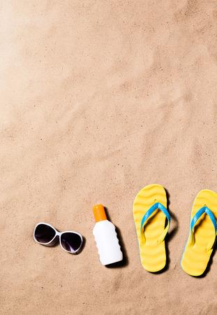 해변에 노란색 플립 플롭 샌들, 선글라스와 선탠 크림 한 쌍의 여름 휴가 조성물. 모래 해변 배경, 스튜디오 촬영, 평면 누워. 공간을 복사합니다.
