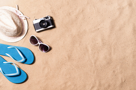 Summer vacation composition with a pair of blue flip flop sandals, hat, sunglasses and retro styled camera laid on a beach. Sand background, studio shot, flat lay. Copy space.
