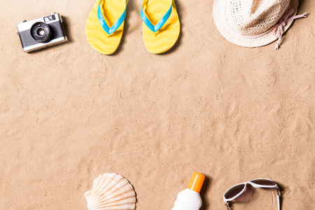 flip flop: Summer vacation composition with pair of yellow flip flop sandals, hat, sunglasses, sun cream and other stuff on a beach. Sand background, studio shot, flat lay. Copy space. Stock Photo