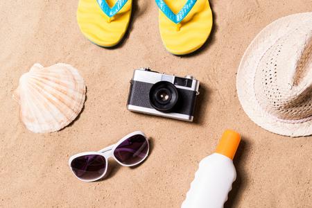 여름 휴가 컴포지션 카메라, 노란색 플립 플롭 샌들, 모자, 선글라스, 태양 크림 및 해변에서 다른 물건 쌍의. 모래 배경, 스튜디오 샷, 평면 누워.