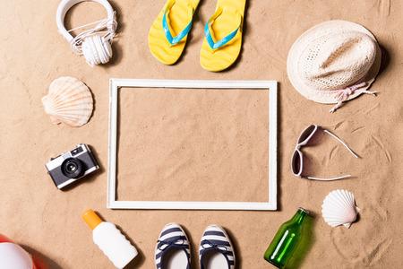 사진 프레임, 노란색 플립 플롭 샌들, 비치 모자, 선글라스, 썬 크림 및 기타 물건의 쌍 여름 휴가 조성물. 모래 배경, 스튜디오 촬영, 평면 누워. 공간을