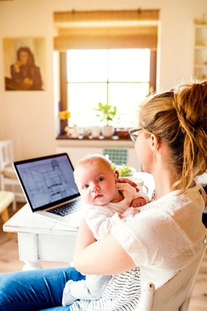 laid: Close up of beautiful mother holding her baby son in the arms, laptop laid on table