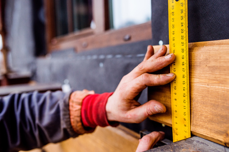 Hands of unrecognizable construction worker thermally insulating house, doing wooden facade, measuring board with yellow tape measure Stock Photo