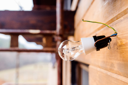 wall socket: Transparent glass light bulb hangs from a spot on wires on brown wooden board wall of the unfinished house.