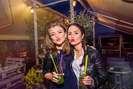 niñas bonitas: Dos hermosas mujeres jóvenes en chaquetas de cuero negro con los cocteles en barra o club que se divierte