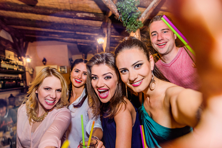 Jonge mooie mensen met cocktails in een bar of club nemen selfie, having fun