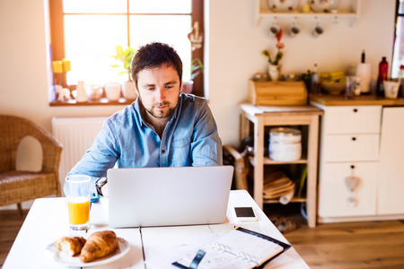 kitchen device: Man sitting at the kitchen table working from home on laptop Stock Photo