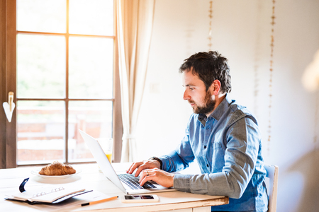 working on laptop: Man sitting at the kitchen table working from home on laptop Stock Photo