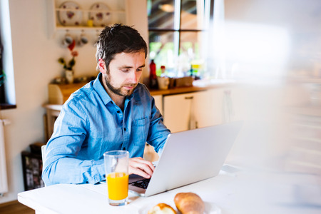 Man sitting at the kitchen table working from home on laptop Stock Photo