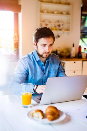 trabajando en casa: Hombre sentado en la mesa de trabajo de la cocina de su casa en la computadora portátil