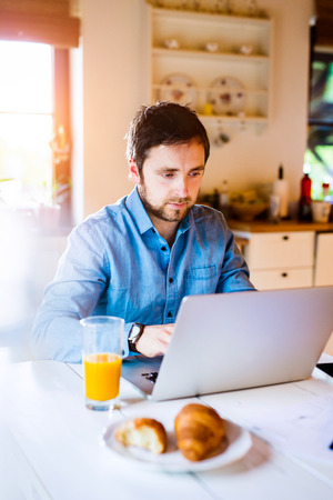 working at home: Man sitting at the kitchen table working from home on laptop Stock Photo