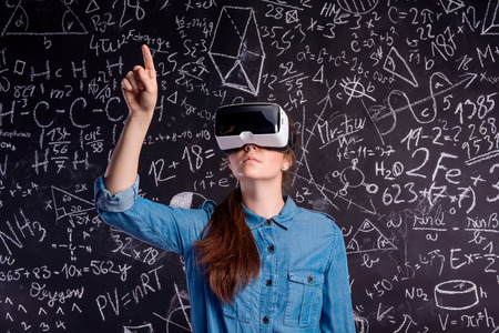 Beautiful woman in blue denim shirt wearing virtual reality goggles, pointing up with finger. Student against big blackboard with mathematical symbols and formulas. Studio shot on black background. Stock Photo