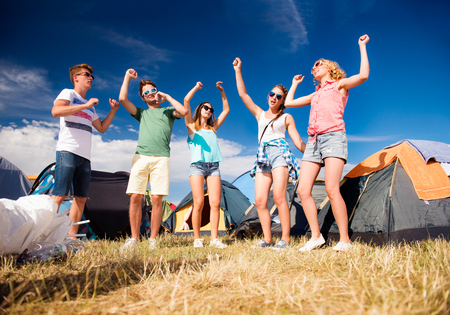 Group of teenage boys and girls at summer music festival, dancing in front of tents, sunny day
