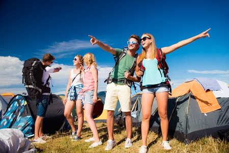 Group of teenage boys and girls with backpacks at summer music festival, showing something, pointing at something, in front of tents