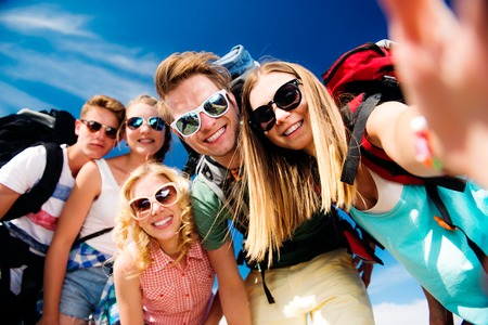 coming together: Group of teenage boys and girls with backpacks at summer music festival taking selfie Stock Photo
