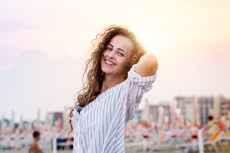 young woman smiling: Beautiful young woman with curly hair on beach wearing striped blue and white shirt, smiling. Enjoying time at seaside. Sunset. Stock Photo