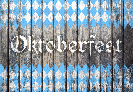 Oktoberfest sign with blue and white rhombus pattern. Wooden background. Studio shot. Stock Photo