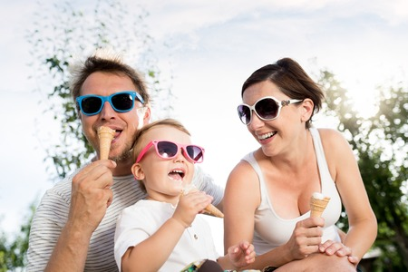 Young parents with their little son in colorful sunglasses eating ice cream, sunny summer garden