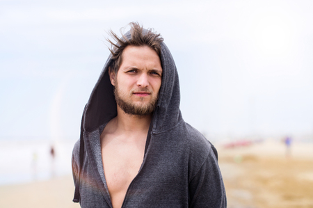 hooded sweatshirt: Hipster man on beach, wearing gray hooded sweatshirt, sunny summer. Enjoying time at seaside. Stock Photo