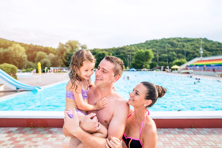 dad and daughter: Young mother and father with their daughter near swimming pool in aqua park. Summer heat and water.