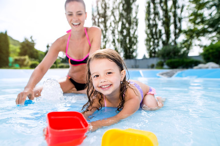 aqua park: Young beautiful mother in bikini playing with her daughter in swimming pool in aqua park. Summer heat and water. Stock Photo
