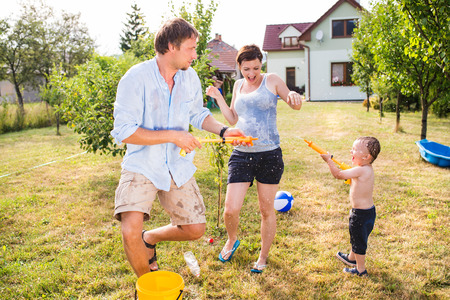 back yard: Little boy with mother and father splashing each other with water gun, fun in garden, sunny summer day, back yard