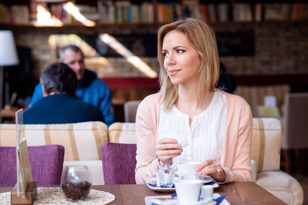 Young beautiful woman in cafe pouring sugar into her coffee, enjoing her espresso and relaxing