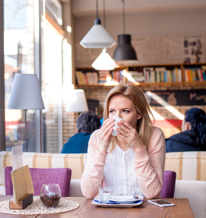 lady with the lamp: Young beautiful woman in cafe drinking coffee, enjoing her espresso and relaxing Stock Photo