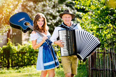 lederhosen: Couple in traditional bavarian clothes standing in the garden in front of wooden fence, playing accordion, holding guitar. Oktoberfest. Stock Photo