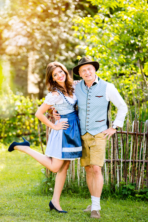wooden fence: Couple in traditional bavarian clothes standing in the garden in front of wooden fence. Oktoberfest. Stock Photo